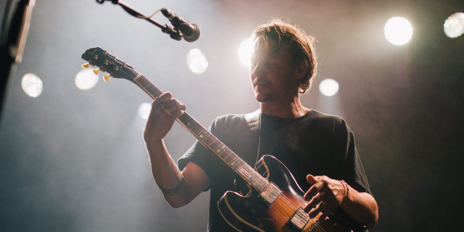 Artist playing a guitar on stage