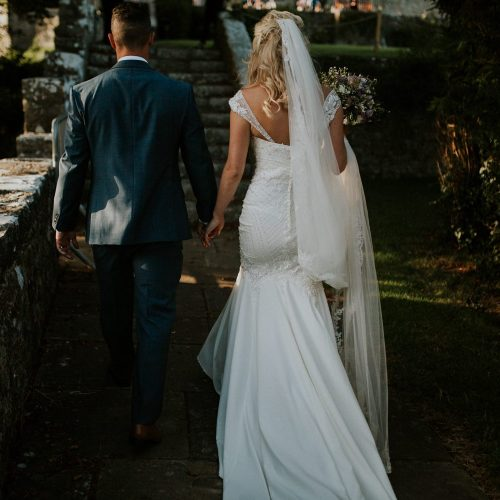 Bride and groom walking at their wedding at St Donat's Castle